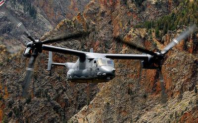 Bell Boeing V-22 Osprey flying between rocky peaks wallpaper