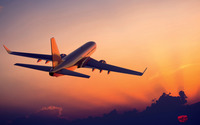Passenger aircraft flying towards the sunset light wallpaper 2560x1440 jpg