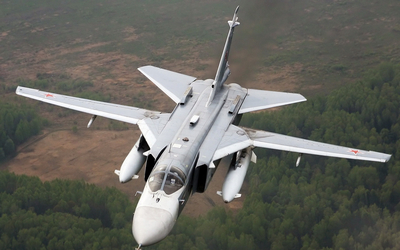 Sukhoi Su-24 flying above a forest wallpaper