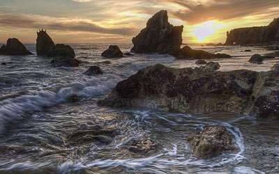 Amazing golden sunset above the rocky beach wallpaper