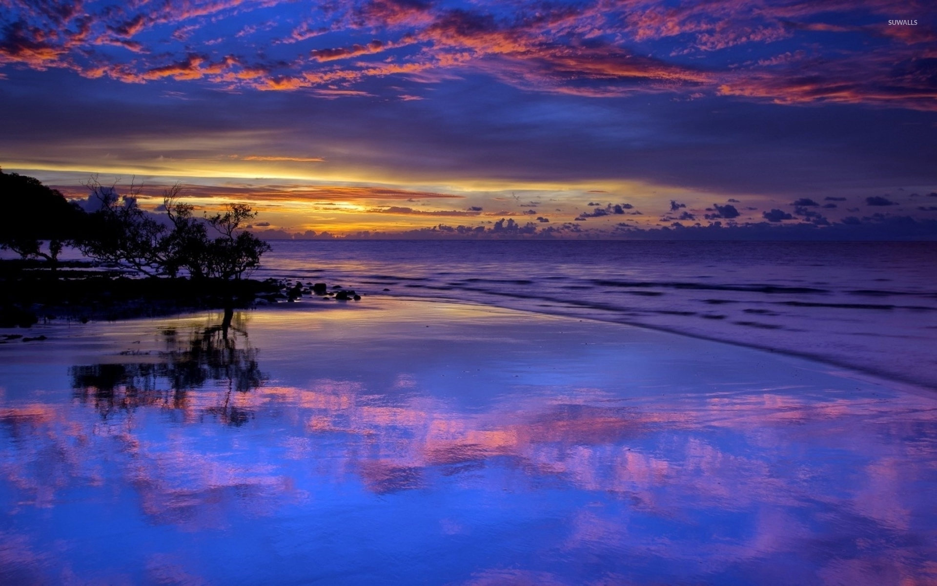 amazing purple sunset clouds reflected in the wet beach