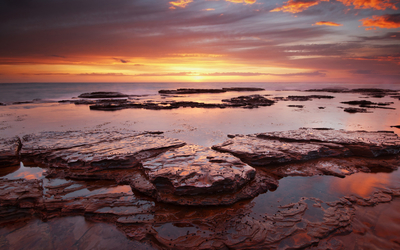 Amazing sunset reflecting in the wet rocky beach Wallpaper