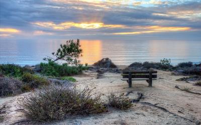 Bench facing the ocean sunset wallpaper