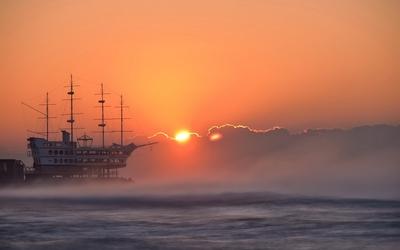 Boat on foggy ocean wallpaper