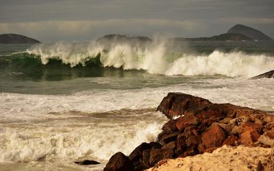 Foamy wave splashing on the rocky shore wallpaper