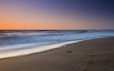 Foamy waves approaching the sandy beach Wallpaper