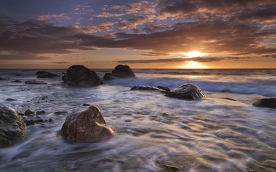 Foamy waves between the rocks at sunset wallpaper