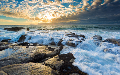Foamy waves splashing in the rocky shore wallpaper