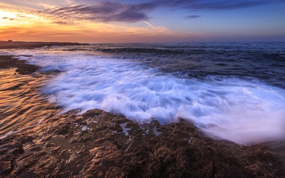 Foamy waves splashing on the rocks wallpaper