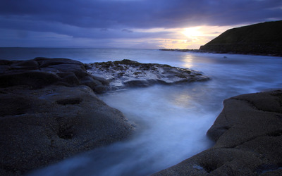 Golden sunset behind the rocky ocean shore wallpaper