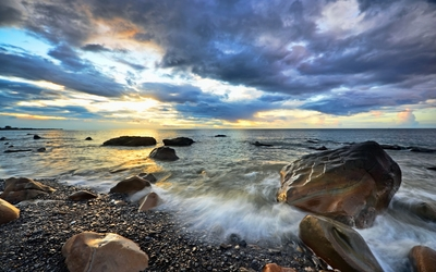 Golden sunset light reflected on the wet rocks on the beach Wallpaper