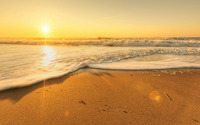Golden sunset light reflecting on the waves reaching to the sand wallpaper 1920x1080 jpg