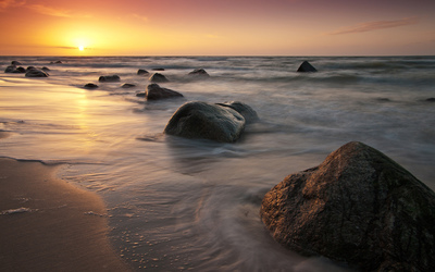 Golden sunset light shining upon the rocks on the beach wallpaper