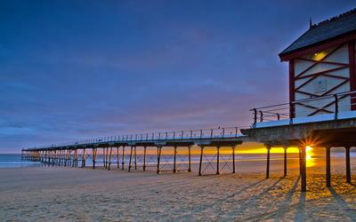 Golden sunset on the ocean pier wallpaper