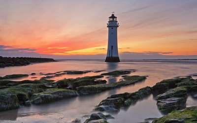 Lighthouse at sunset near the mossy coast wallpaper