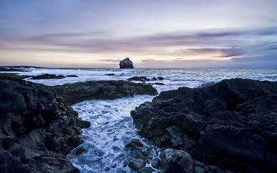Lonesome rocky peak rising from the wavy ocean wallpaper