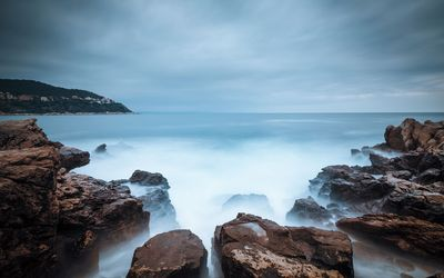 Misty water reaching to the rocky shore wallpaper