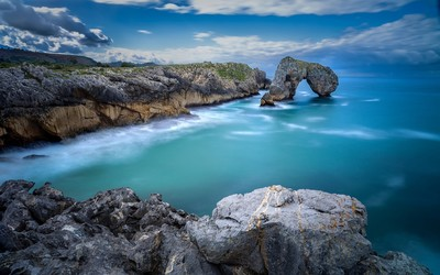 Mossy rock natural arch in the ocean wallpaper