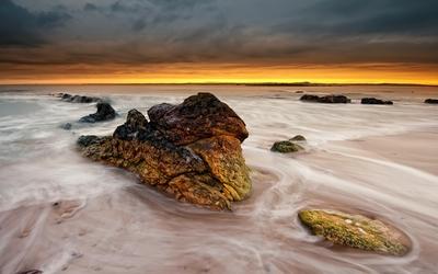 Mossy rocks in the ocean water wallpaper