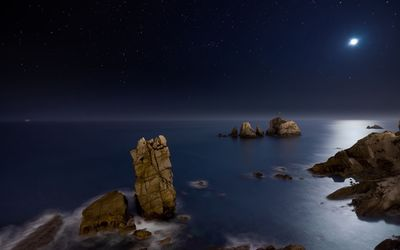 Ocean rocks rising to the moonlight wallpaper
