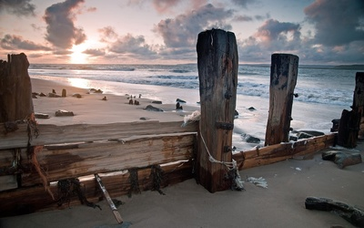 Ocean waves reaching to the wooden pillars on the beach wallpaper