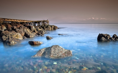 Pier on the rocky ocean shore Wallpaper