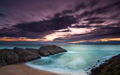 Purple clouds above the rocky ocean shore wallpaper