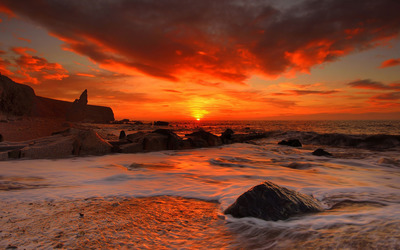 Red sunset above the rocky beach wallpaper