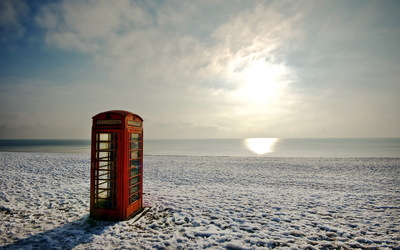 Red telephone booth on a winter beach wallpaper