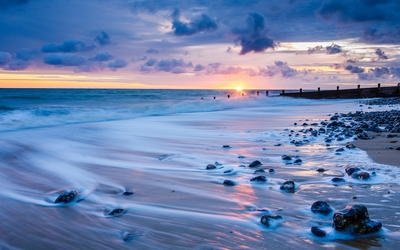 Rocks on a sandy beach wallpaper