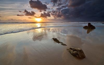 Rocks on a sandy beach facing the sunset wallpaper