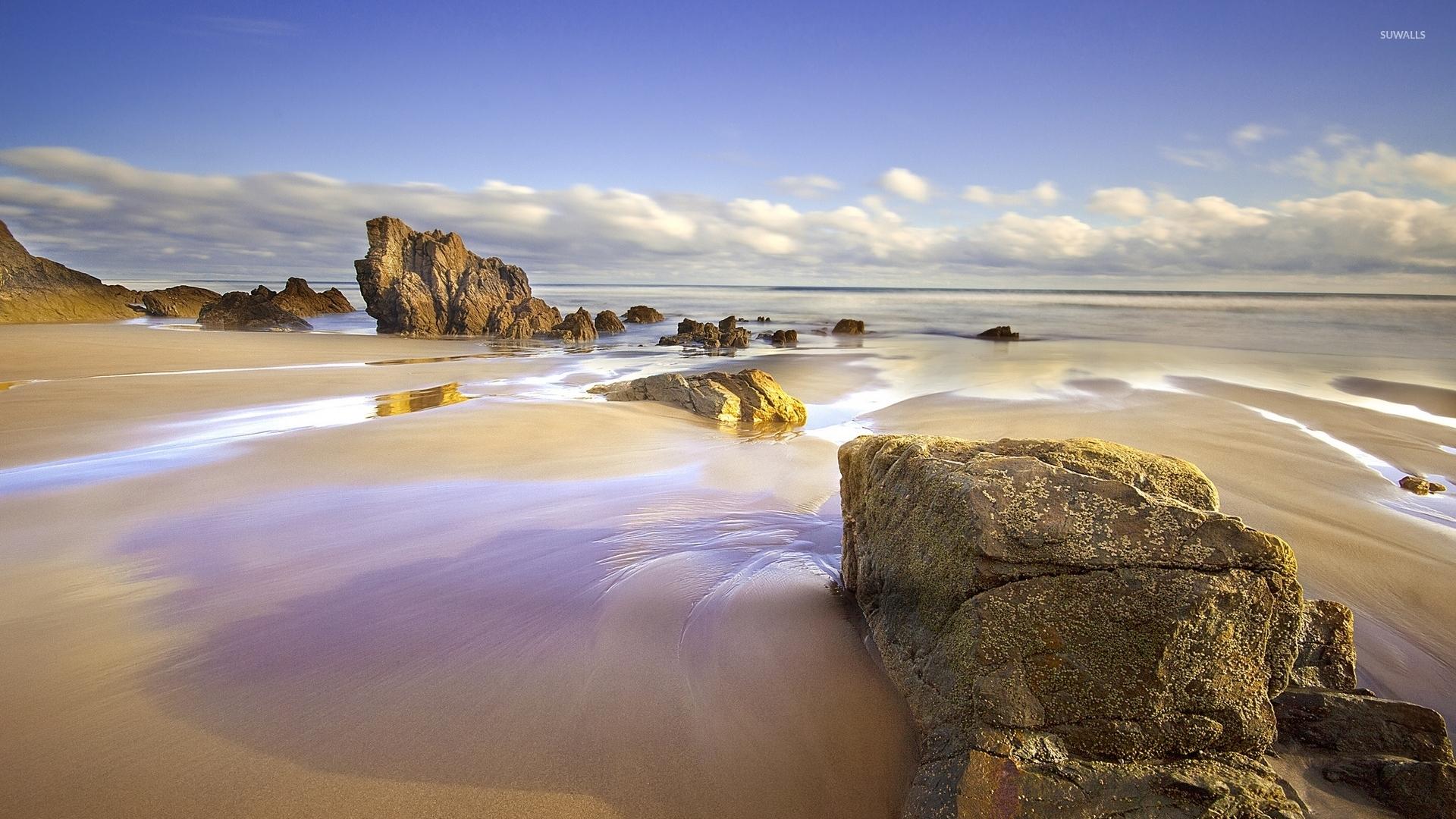 Sandy Beach Wallpaper: Rocks On A Wet Sandy Beach Wallpaper