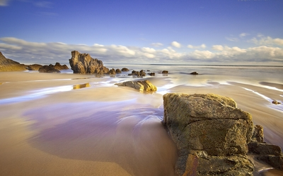 Rocks on a wet sandy beach wallpaper