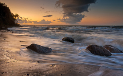 Rocks on the beach facing the whirling waves at sunset wallpaper