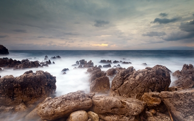 Rocks rising from the misty ocean water towards the sunset Wallpaper