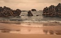 Rocks rising from the water near the sandy beach wallpaper 1920x1200 jpg