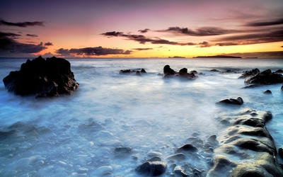 Rocks rising towards the sunset from the mysterious ocean wallpaper