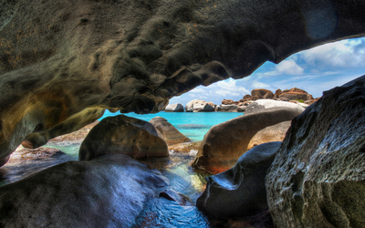 Rocky cave entrance by the ocean Wallpaper