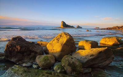 Rocky island near rocky beach wallpaper