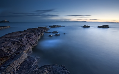 Rocky shore bathing in the calm ocean water wallpaper