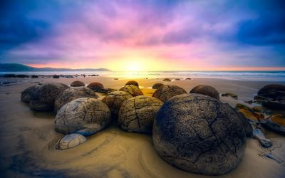 Rounded rocks on sandy beach wallpaper