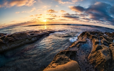 Rounded rocky shore bathing in the warm sunset sun Wallpaper