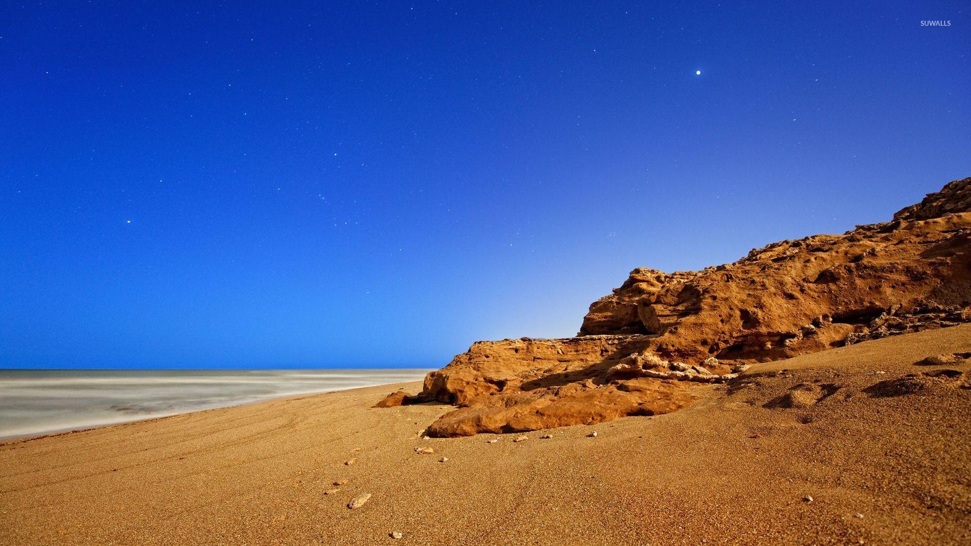 Sandy Beach Wallpaper: Rusty Rock On Sandy Beach Wallpaper