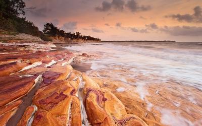 Rusty rocks washed by the foamy ocean waves Wallpaper