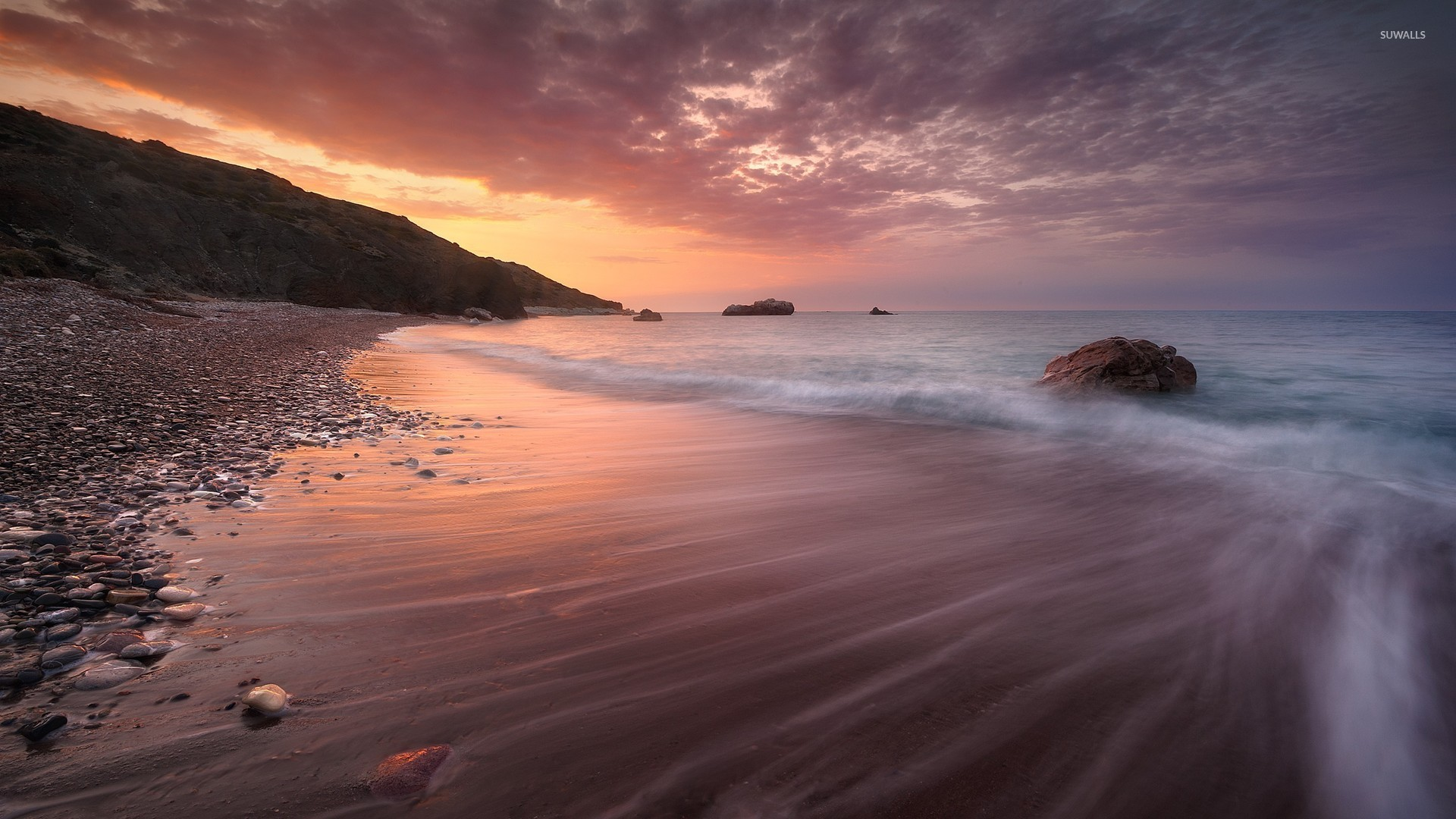 Sandy Beach Wallpaper: Sandy Beach Splitting The Ocean From The Rocks Wallpaper