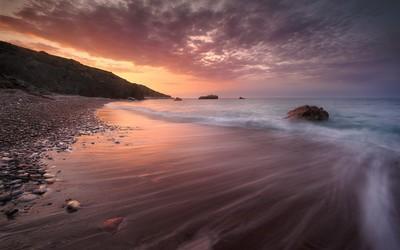 Sandy beach splitting the ocean from the rocks Wallpaper