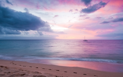 Small boat in the ocean at sunset Wallpaper