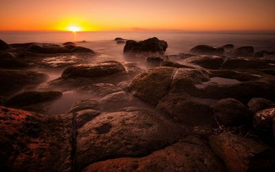Sunset over the rocky shore wallpaper