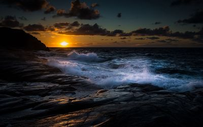 Waves fighting with the rocky shore at sunset wallpaper