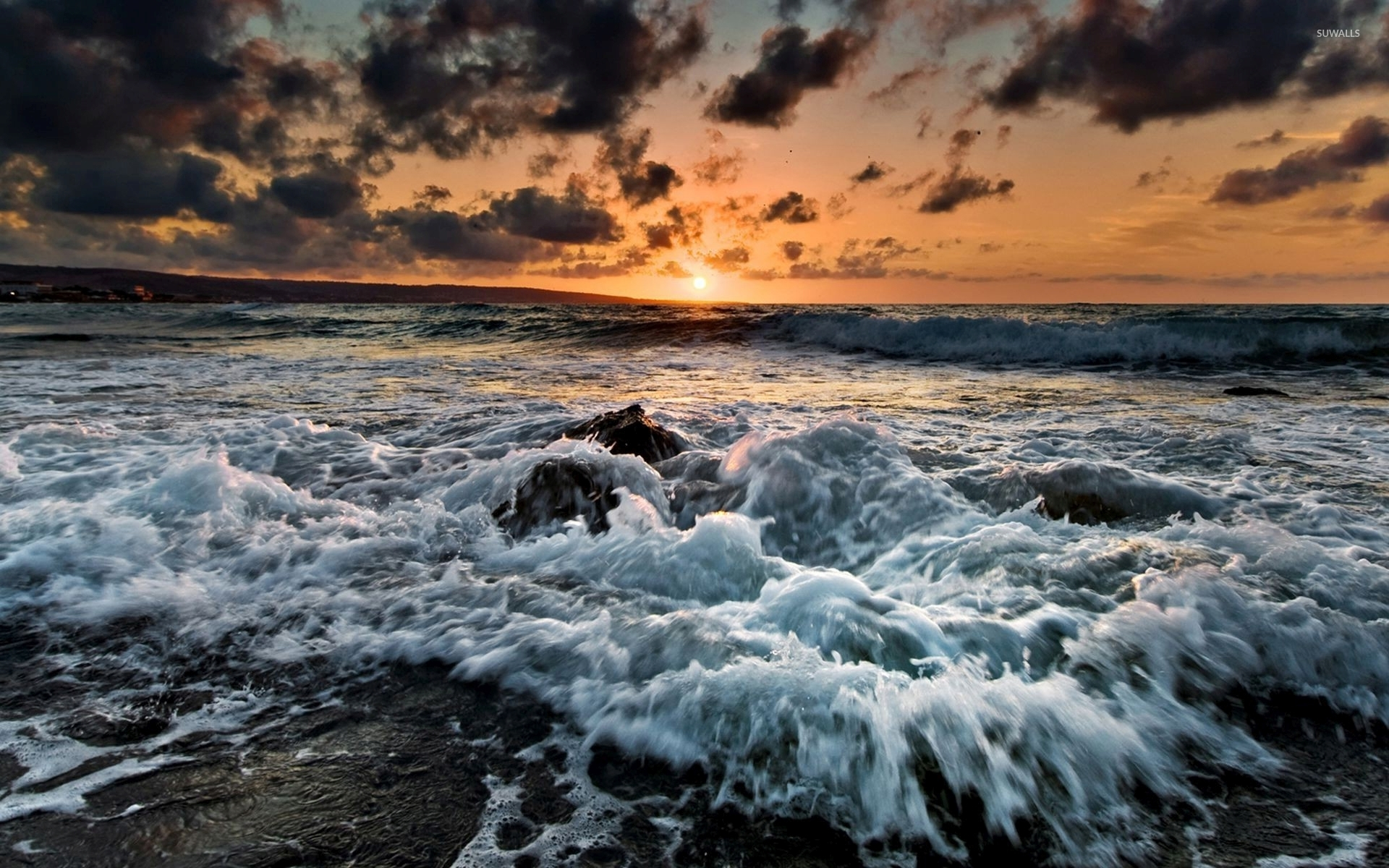 Waves Reaching The Rocky Beach At Sunset Wallpaper